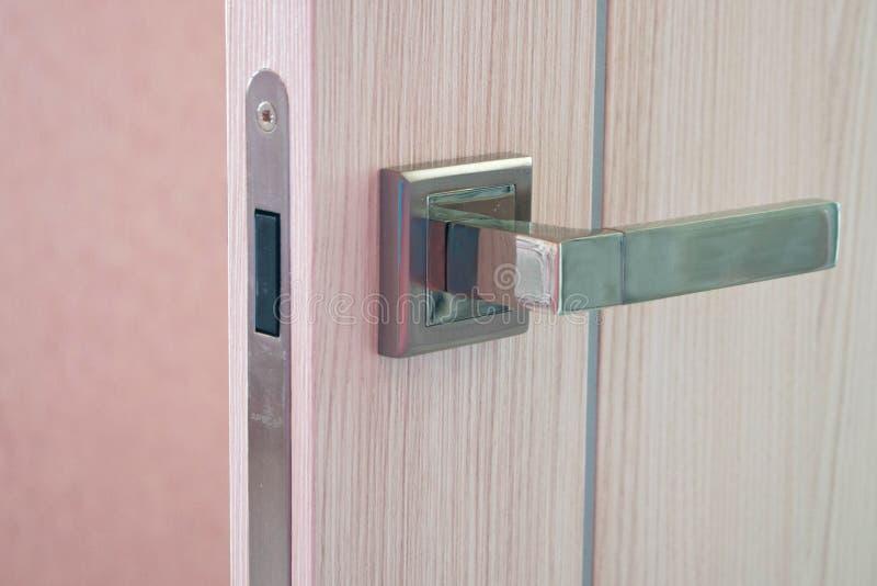 Ανοιχτή πόρτα στο σύγχρονο σπίτι Σύγχρονη ξύλινη πόρτα με τη λεπτομέρεια κινηματογραφήσεων σε πρώτο πλάνο λαβών μετάλλων Εσωτερικ στοκ φωτογραφία