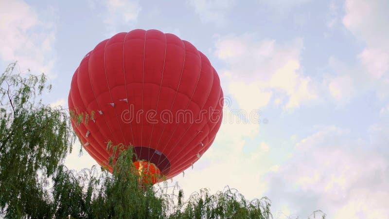 Ανοιχτό κόκκινο - μπαλόνι ζεστού αέρα που πετά πέρα από τα δέντρα, καταπληκτική άποψη, ακραίος ελεύθερος χρόνος στοκ φωτογραφίες