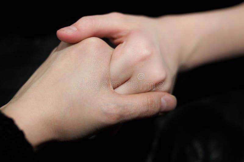Αντέχοντας ένα χέρι βοηθείας, τα χέρια δύο ανθρώπων, ένας που βοηθούν άλλο, σε ένα σκοτεινό κλίμα στοκ εικόνες