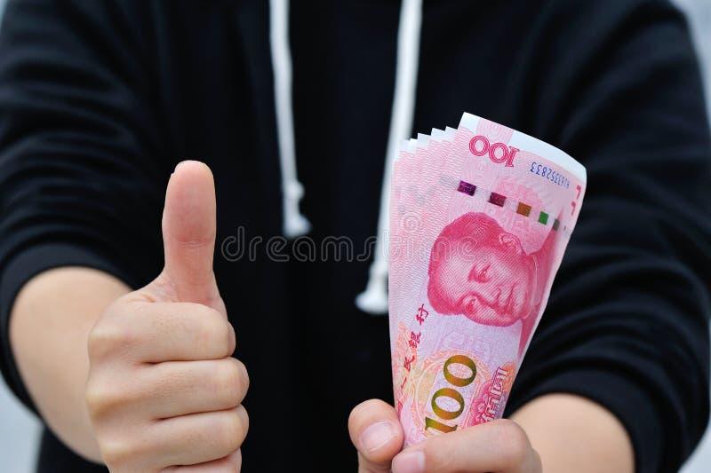 Αντίχειρας επάνω και κινεζικός yuan διαθέσιμος στοκ εικόνες