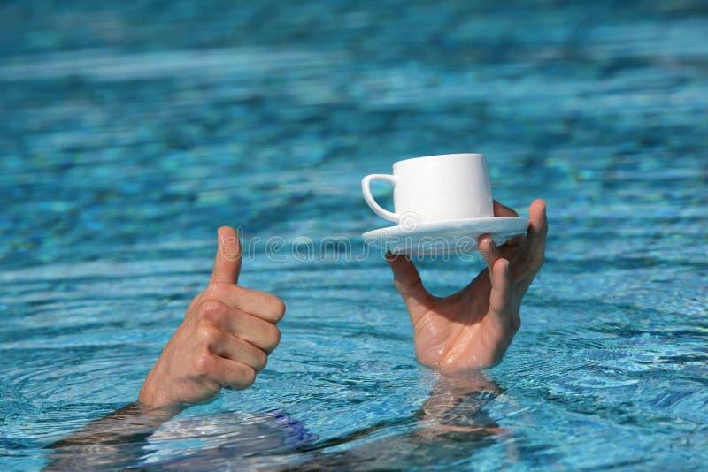 Αντίχειρας επάνω στη χειρονομία - χέρι ανωτέρω - φλιτζάνι του καφέ εκμετάλλευσης νερού στοκ φωτογραφία με δικαίωμα ελεύθερης χρήσης