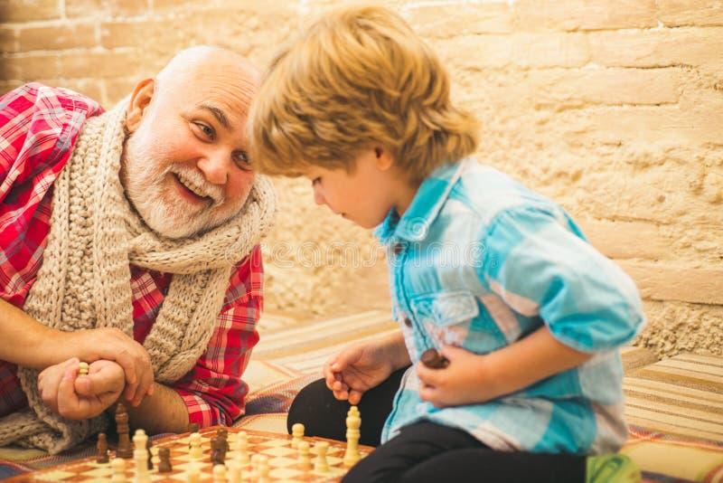 Ανταγωνισμός σκακιού Χαριτωμένο αγόρι που αναπτύσσει τη στρατηγική σκακιού Σκάκι παιχνιδιού παππούδων και εγγονών Παππούς και εγγ στοκ φωτογραφίες