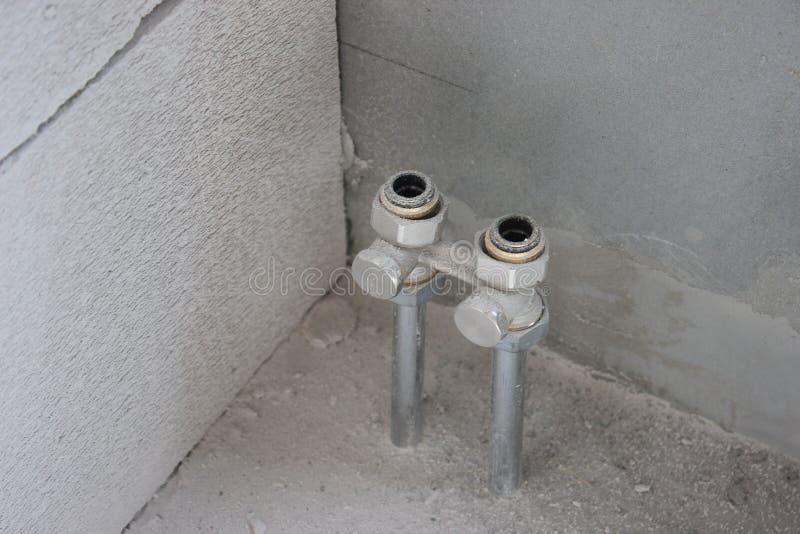 Ανταλλάκτης θερμότητας σωληνώσεων επίπεδος δύο σωλήνες προεξέχουν από το πάτωμα κατά τη διάρκεια των επισκευών στον τοίχο η αντικ στοκ φωτογραφίες