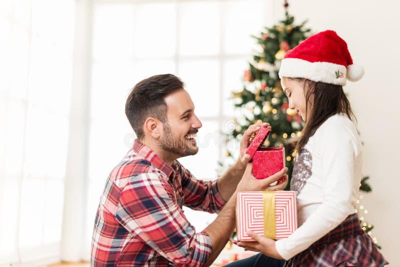 Ανταλλάσσοντας και ανοίγοντας χριστουγεννιάτικα δώρα πατέρων και κορών στοκ εικόνα