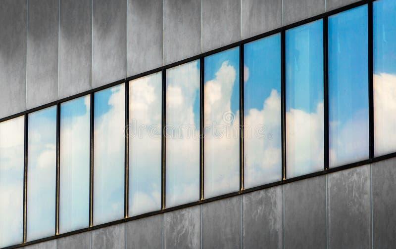 Αντανάκλαση του μπλε ουρανού και των άσπρων σύννεφων στα παράθυρα ενός γκρίζου συγκεκριμένου κτηρίου στοκ εικόνες με δικαίωμα ελεύθερης χρήσης