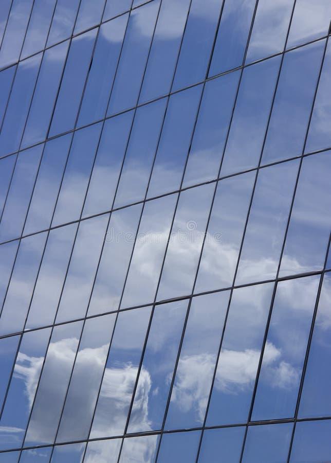 Αντανάκλαση του ουρανού με τα σύννεφα στα παράθυρα γυαλιού του κτηρίου στοκ φωτογραφία