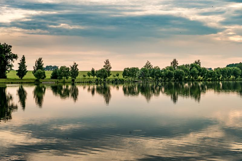 Αντανάκλαση των δέντρων σε ένα νερό λιμνών σε ένα ήρεμο θερινό βράδυ στοκ φωτογραφίες με δικαίωμα ελεύθερης χρήσης
