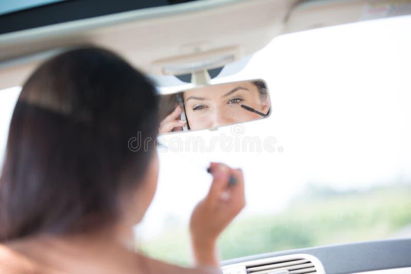 Αντανάκλαση της γυναίκας που χρησιμοποιεί το τηλέφωνο κυττάρων εφαρμόζοντας mascara στον οπισθοσκόπο καθρέφτη του αυτοκινήτου στοκ φωτογραφία