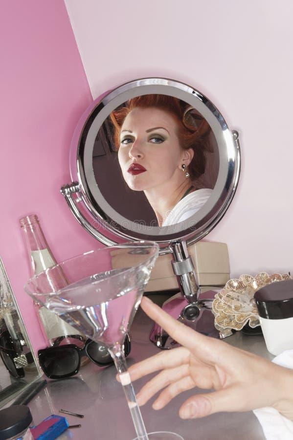 Αντανάκλαση της όμορφης γυναίκας στον καθρέφτη με martini το γυαλί στον πίνακα στοκ εικόνα