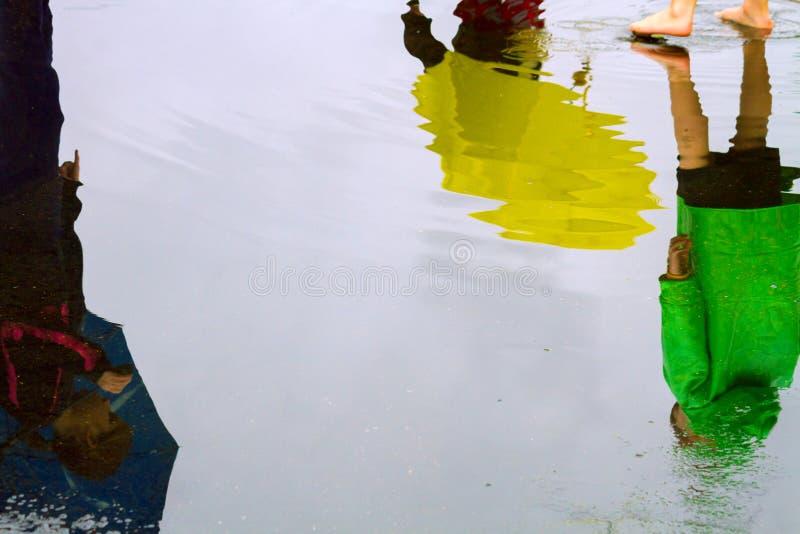 Αντανακλάσεις τριών παιδιών που περπατούν σε μια λακκούβα με Raingear και στοκ φωτογραφία με δικαίωμα ελεύθερης χρήσης