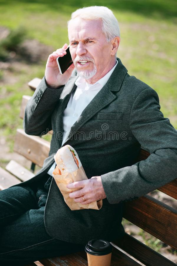 Αντανακλαστικός ανώτερος επιχειρηματίας που γευματίζει με το σάντουιτς στοκ φωτογραφία με δικαίωμα ελεύθερης χρήσης