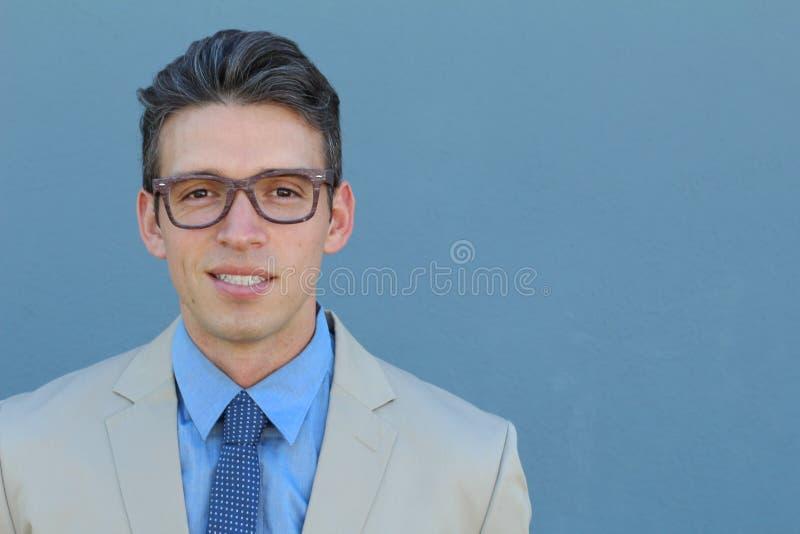 Αντιμετωπίζοντας τη ζωή σοβαρά Πορτρέτο του όμορφου νεαρού άνδρα σε formalwear με τα φανταχτερά γυαλιά στεμένος στο μπλε κλίμα στοκ εικόνα