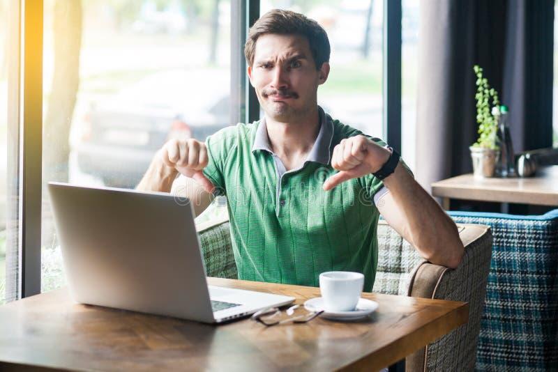 Αντιπάθεια! Νεαρός δυσαρεστημένος επιχειρηματίας με πράσινο μπλουζάκι που κάθεται, εργάζεται στο φορητό υπολογιστή, κοιτάζει την  στοκ εικόνες