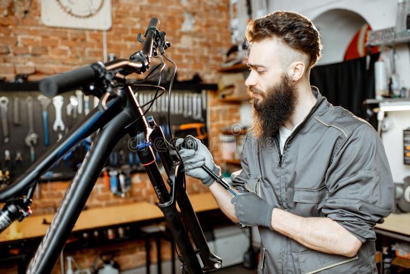 Αντλώντας δίκρανο ποδηλάτων Reapairman στο εργαστήριο στοκ φωτογραφία