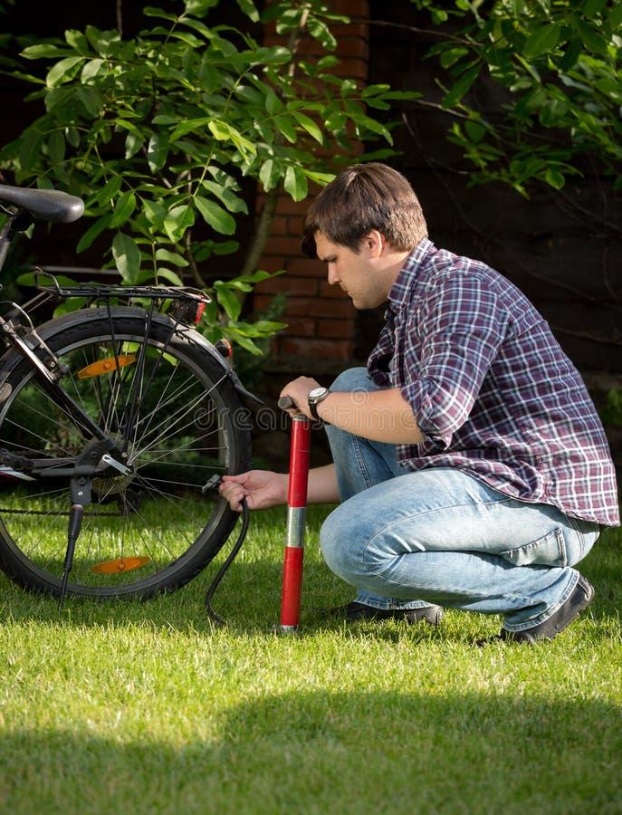 Αντλώντας ρόδα ποδηλάτων νεαρών άνδρων με την αεραντλία στοκ εικόνα με δικαίωμα ελεύθερης χρήσης