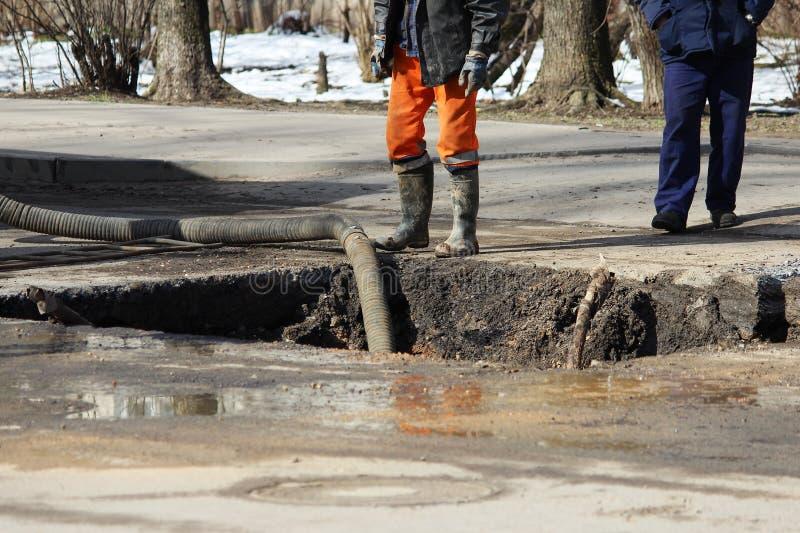 Αντλώντας νερό από το κοίλωμα κατά τον εξάλειψη ενός ατυχήματος: ρήξη των σωλήνων με το κρύο νερό στοκ εικόνες