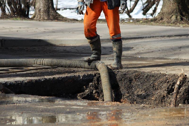 Αντλώντας νερό από το κοίλωμα κατά τον εξάλειψη ενός ατυχήματος: ρήξη των σωλήνων με το κρύο νερό στοκ φωτογραφία με δικαίωμα ελεύθερης χρήσης