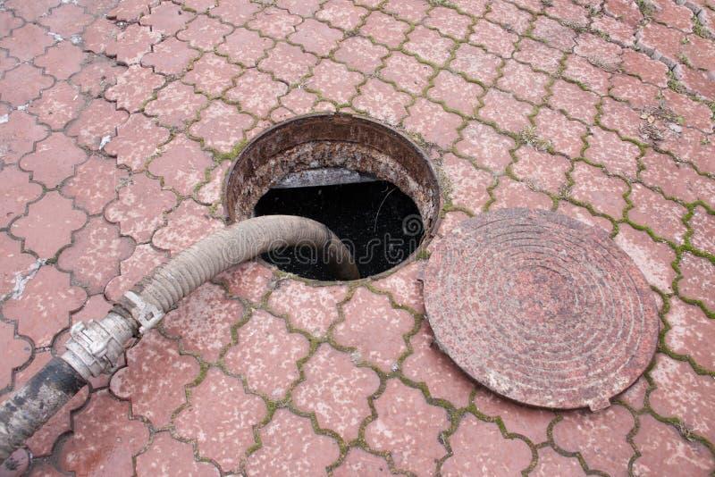Αντλώντας λύματα από την τρύπα αγωγών στοκ φωτογραφία με δικαίωμα ελεύθερης χρήσης