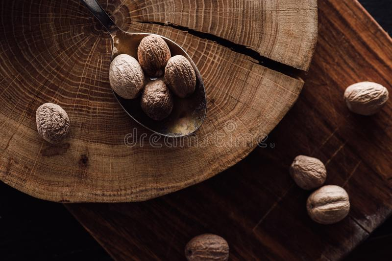 ανυψωμένη άποψη του τεμνόντων πίνακα και του κουταλιού με το σωρό των nutmegs στοκ εικόνες με δικαίωμα ελεύθερης χρήσης