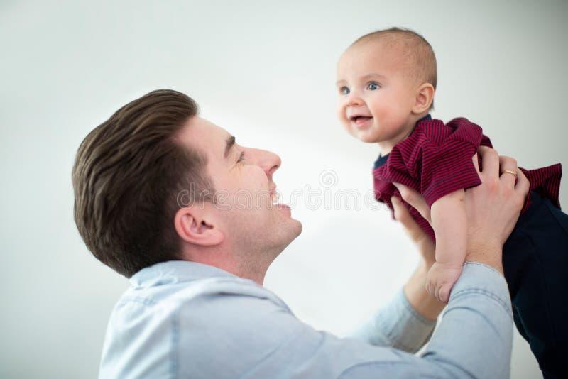 Ανυψωτικός χαμογελώντας γιος μωρών πατέρων στον αέρα στο σπίτι δεδομέ στοκ εικόνες με δικαίωμα ελεύθερης χρήσης