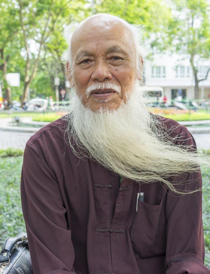 Ανόι, Βιετνάμ - 3 Μαΐου 2014: Πορτρέτο ενός ηληκιωμένου με τη μακροχρόνια άσπρη συνεδρίαση γενειάδων στο πάρκο στο Ανόι, Βιετνάμ στοκ φωτογραφία με δικαίωμα ελεύθερης χρήσης