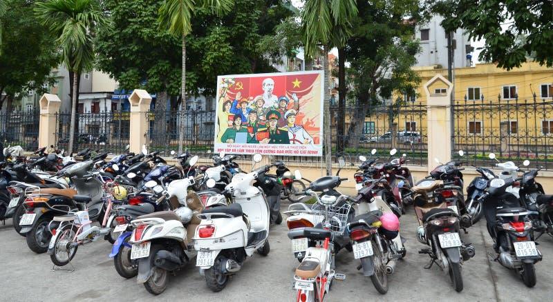 Ανόι Βιετνάμ - Marz 1, 2015: Πολλά μηχανικά δίκυκλα μπροστά από τους πίνακες διαφημίσεων προπαγάνδας στοκ εικόνα με δικαίωμα ελεύθερης χρήσης