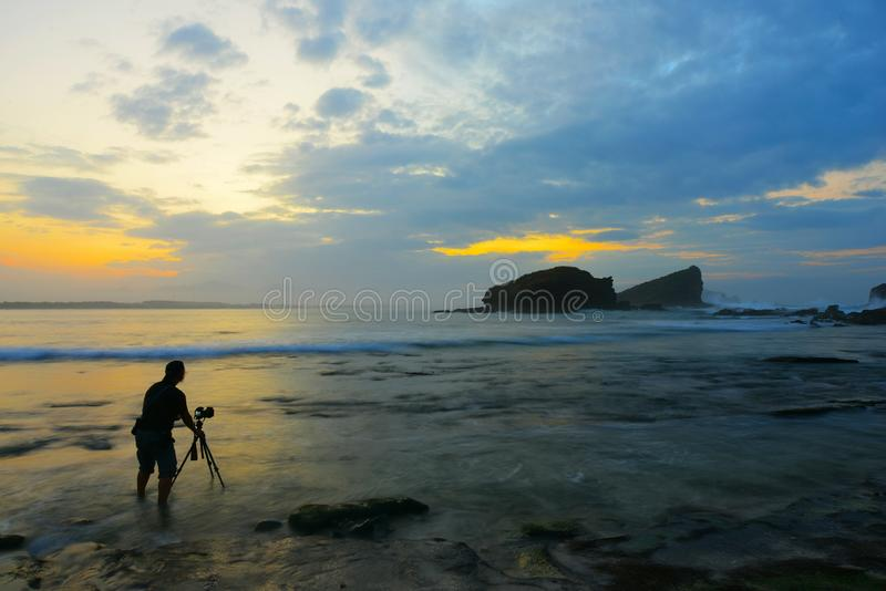 Ανύψωση του ήλιου με το Rock στη μέση της θάλασσας με ομαλό κύμα στοκ φωτογραφία