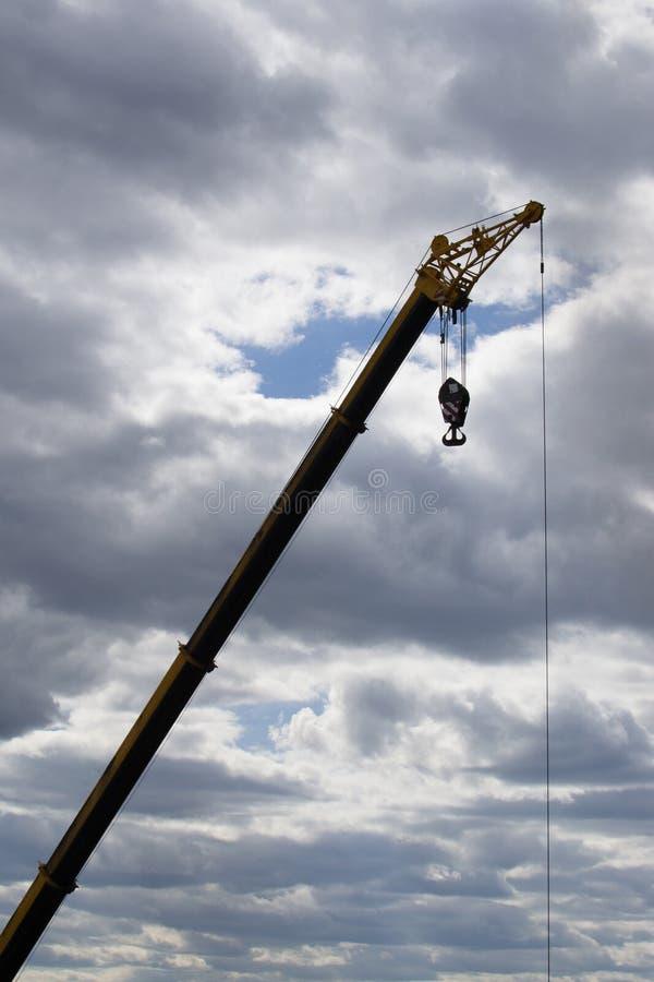 Ανύψωση του γερανού σε ένα εργοτάξιο οικοδομής ενάντια σε έναν νεφελώδη ουρανό στοκ εικόνες
