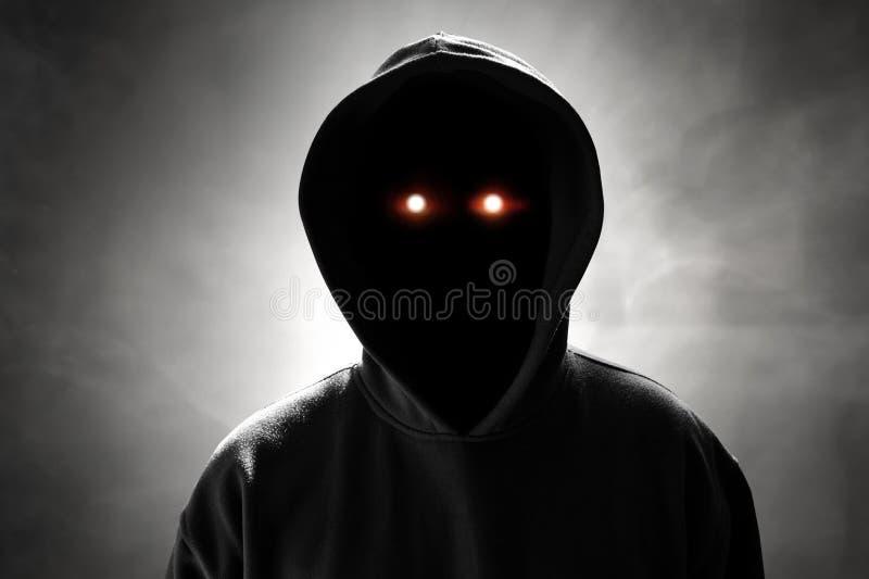 Ανώνυμος χάκερ που στέκεται στο υπόβαθρο καπνού στοκ εικόνες