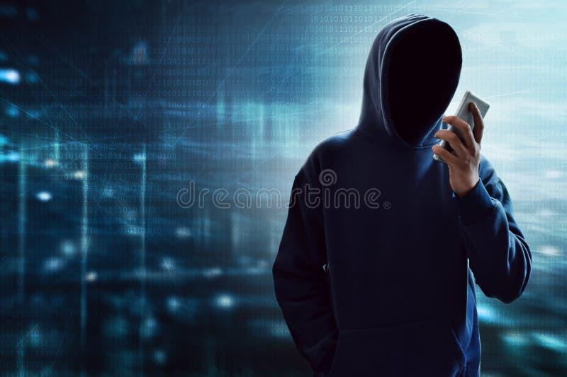 Ανώνυμος χάκερ που χρησιμοποιεί το κινητό τηλέφωνο στοκ φωτογραφίες