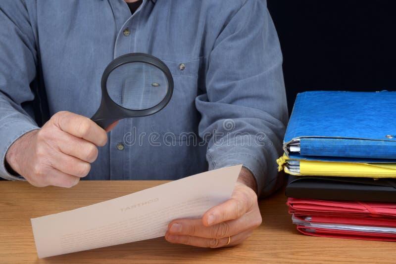 Ανώνυμο άτομο που διαβάζει μια σύμβαση κάτω από μια ενίσχυση - γυαλί στοκ φωτογραφίες με δικαίωμα ελεύθερης χρήσης