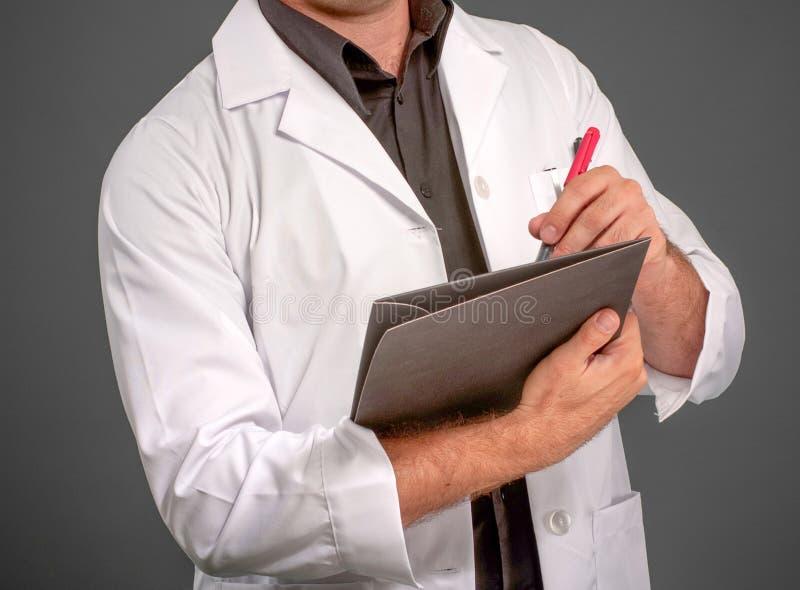 Ανώνυμο άτομο στο γράψιμο παλτών εργαστηρίων στοκ φωτογραφία με δικαίωμα ελεύθερης χρήσης