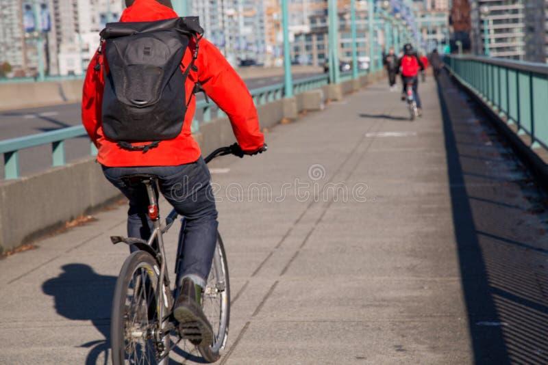 Ανώνυμο αρσενικό μαύρο σακίδιο πλάτης σακακιών bicyclist κόκκινο που οδηγά τη σύγχρονη πόλη στοκ φωτογραφίες με δικαίωμα ελεύθερης χρήσης