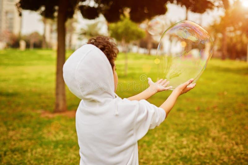 Ανώνυμο παιχνίδι παιδιών με τη φυσαλίδα σαπουνιών την ηλιόλουστη ημέρα στοκ φωτογραφία με δικαίωμα ελεύθερης χρήσης