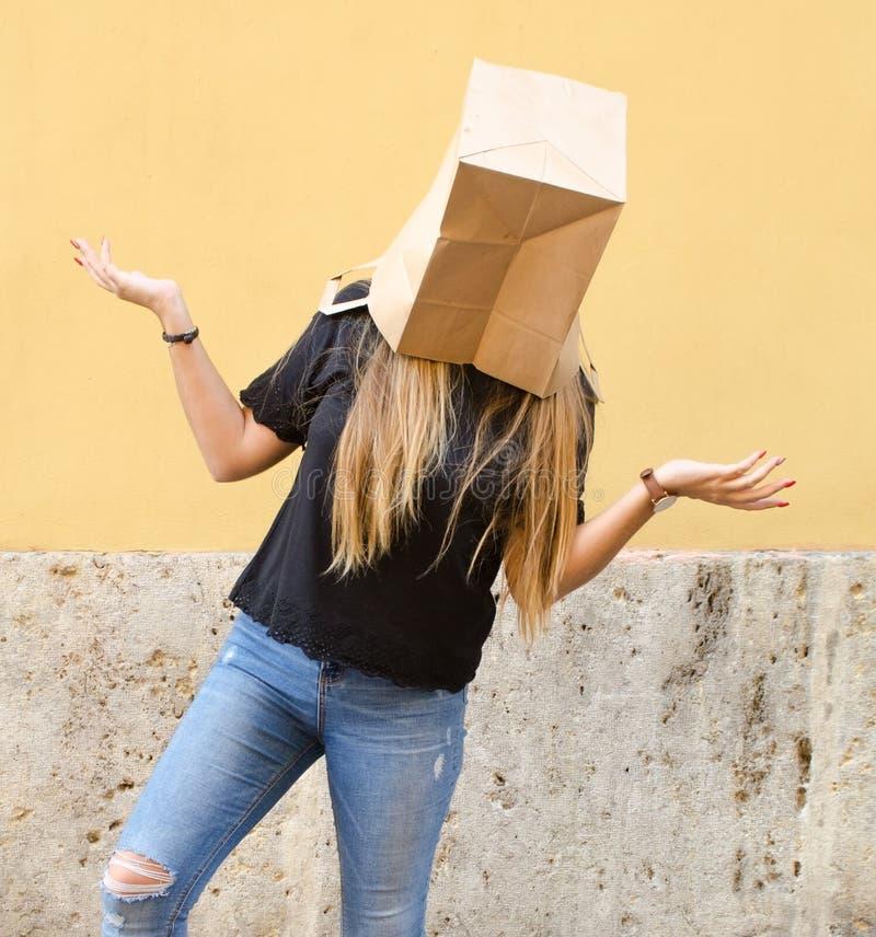 Ανώνυμο πρόσωπο που φορά μια τσάντα εγγράφου πέρα από το κεφάλι της μπροστά από το κίτρινο υπόβαθρο στοκ φωτογραφίες