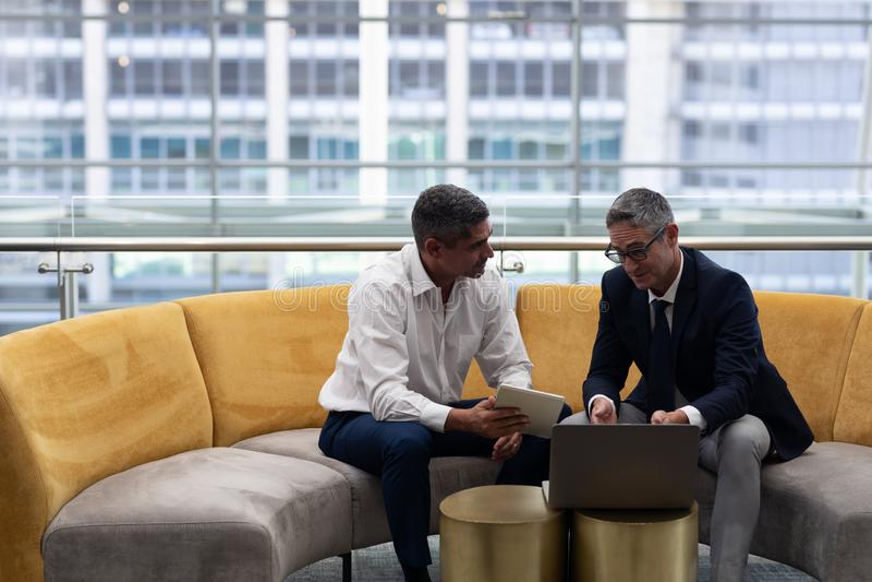 Ανώτατα στελέχη επιχείρησης Καυκασίων που μιλούν τη συζήτηση πέρα από το lap-top καθμένος στον καναπέ στοκ εικόνα με δικαίωμα ελεύθερης χρήσης