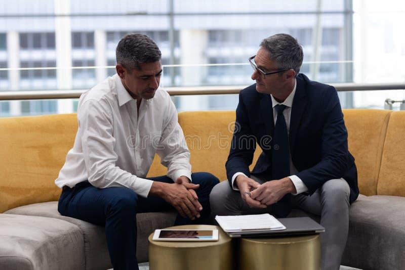 Ανώτατα στελέχη επιχείρησης Καυκασίων που μιλούν το ένα με το άλλο στον καναπέ στοκ φωτογραφία με δικαίωμα ελεύθερης χρήσης
