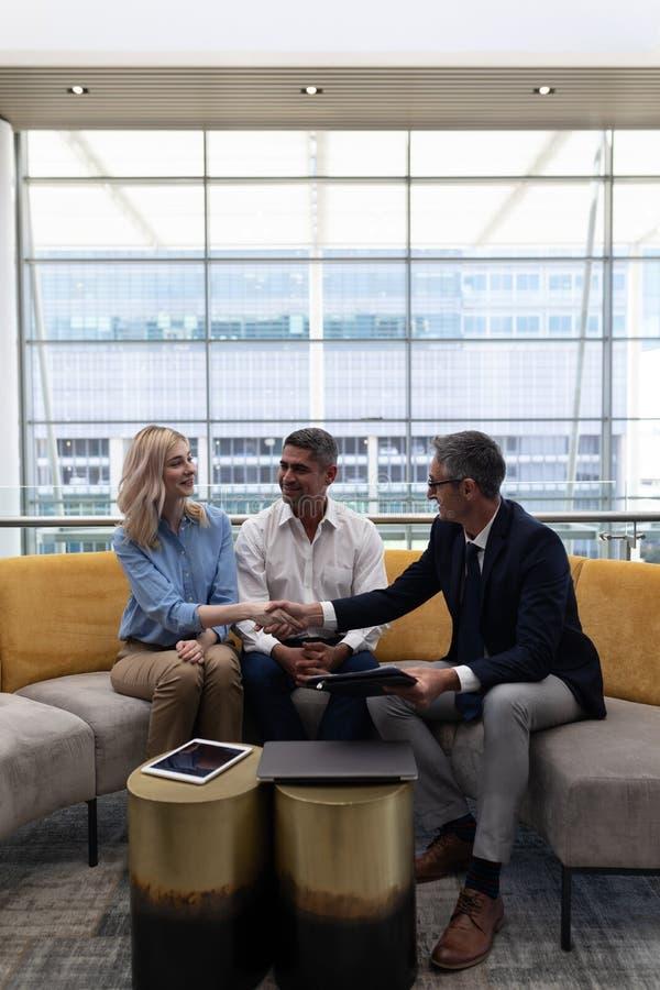 Ανώτατα στελέχη επιχείρησης Καυκασίων που τινάζουν το χέρι καθμένος στον καναπέ στοκ φωτογραφία με δικαίωμα ελεύθερης χρήσης