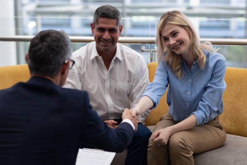 Ανώτατα στελέχη επιχείρησης Καυκασίων που τινάζουν το χέρι καθμένος στον καναπέ στοκ εικόνες