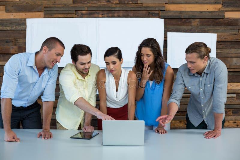 Ανώτατα στελέχη επιχείρησης που συζητούν πέρα από το lap-top στοκ εικόνες