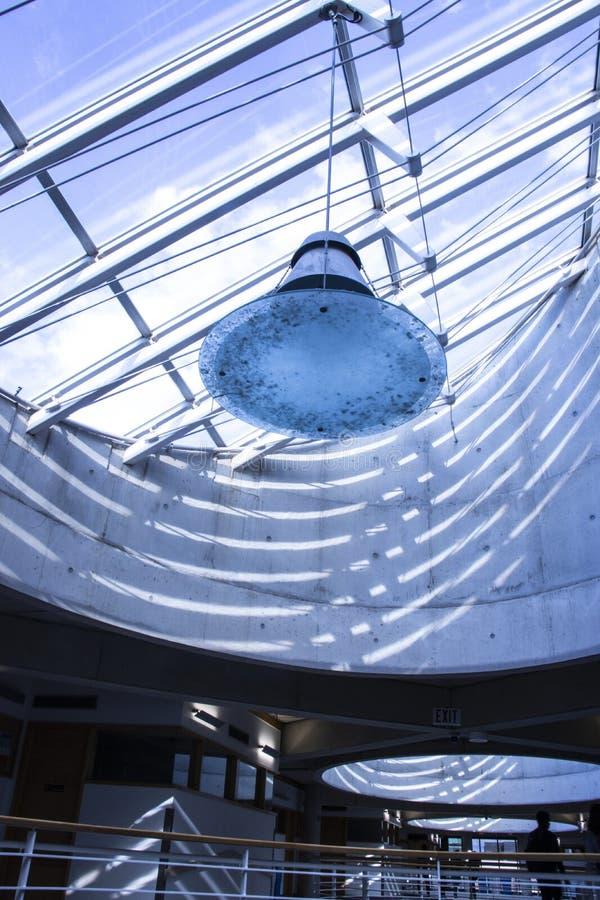 Ανώτατο όριο και συμπαγείς τοίχοι γυαλιού σε ένα σύγχρονο κτήριο με το μεγάλο φωτισμό στοκ φωτογραφία