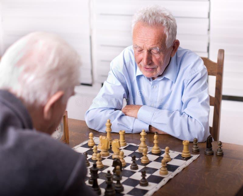 Ανώτερα άτομα που παίζουν το σκάκι στοκ εικόνα