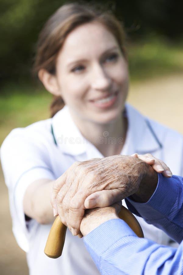Ανώτερα ανθρώπινα χέρια που στηρίζονται στον εργαζόμενο περπατώντας ραβδιών με προσοχή μέσα στοκ φωτογραφίες