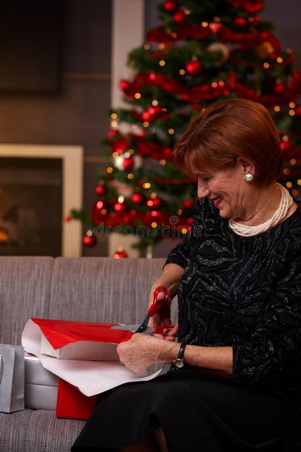 Ανώτερα τυλίγοντας χριστουγεννιάτικα δώρα γυναικών στοκ εικόνα
