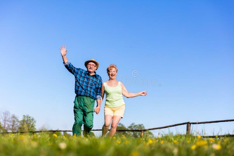 Ανώτερα χέρια εκμετάλλευσης ζευγών και τρέξιμο υπαίθρια στοκ φωτογραφία με δικαίωμα ελεύθερης χρήσης