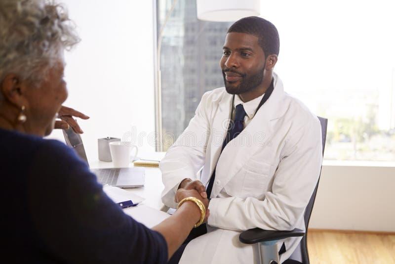 Ανώτερα χέρια τινάγματος γυναικών με τον αρσενικό καλλυντικό χειρούργο γιατρών στην αρχή στοκ φωτογραφία
