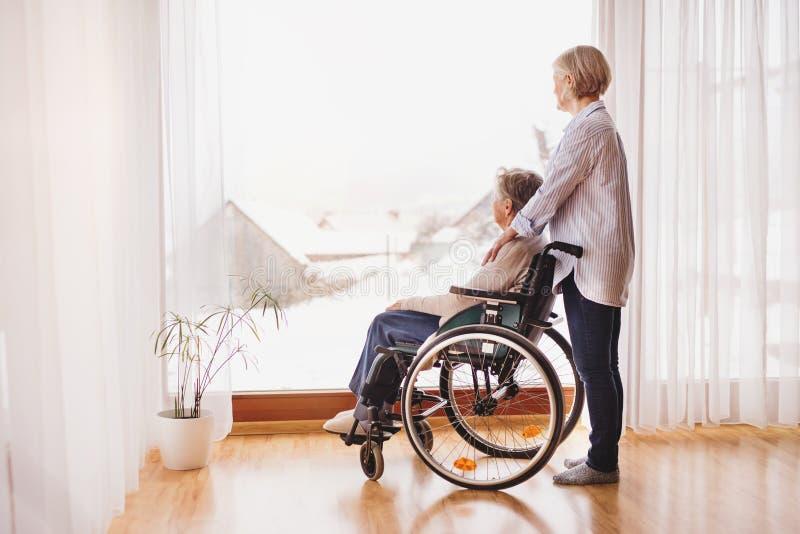 Ανώτερες γυναίκες με την αναπηρική καρέκλα στο σπίτι στοκ φωτογραφία με δικαίωμα ελεύθερης χρήσης