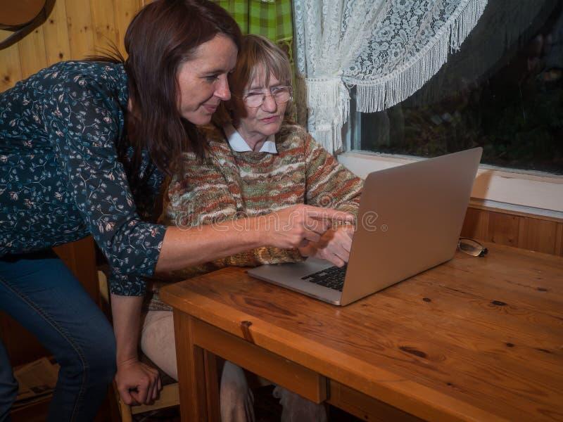 Ανώτερες και ώριμες γυναίκες που χρησιμοποιούν ένα lap-top στοκ εικόνα