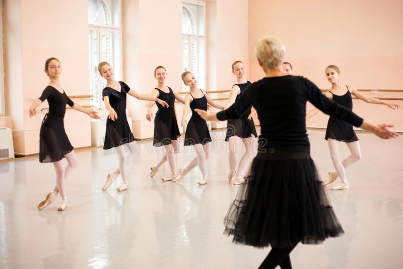 Ανώτερες καταδεικνύοντας κινήσεις εκπαιδευτικών μπαλέτου μπροστά από μια ομάδα έφηβη στοκ εικόνες με δικαίωμα ελεύθερης χρήσης