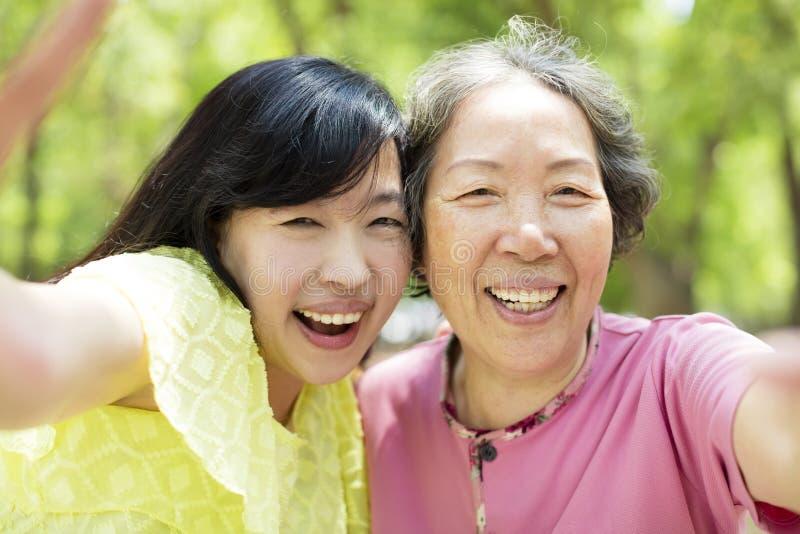 Ανώτερες μητέρα και κόρη που παίρνουν selfie στοκ εικόνα